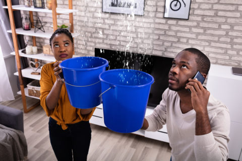 Couple using buckets to catch flood water in house